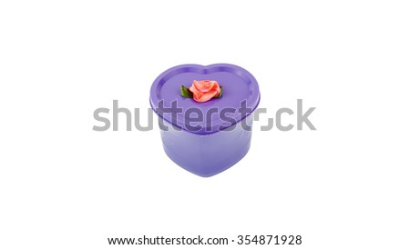 Purple love shape plastic container with plastic flower isolated on white background. - stock photo