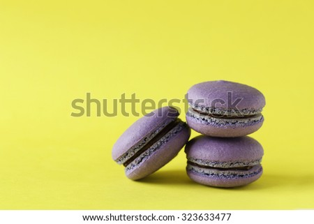 Purple macarons on yellow paper background