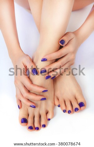 Purple Manicure and Pedicure. Makeup, fashion, beauty. Beautiful female sexy legs with purple pedicure and hands with manicure - stock photo