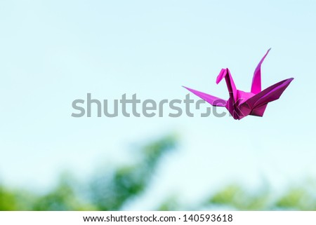 purple paper bird origami crane on sky - stock photo