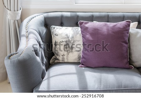 purple pillow on classic sofa style in living room at home - stock photo