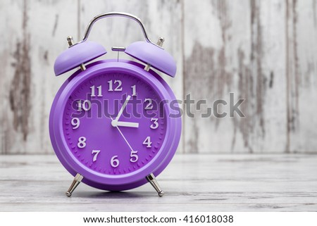 Purple retro alarm clock on white wooden background - stock photo