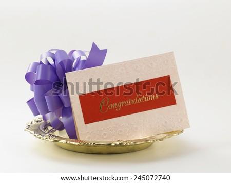 purple ribbon bow and a congratulation card - stock photo