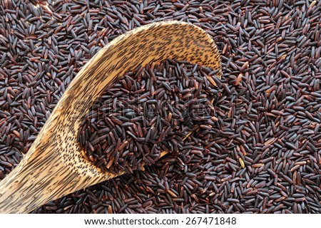 purple rice on wooden spoon with purple rice background
