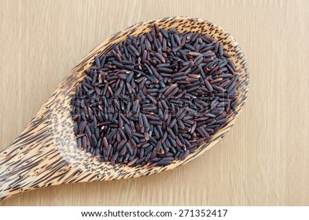 purple rice on wooden spoon with wooden background