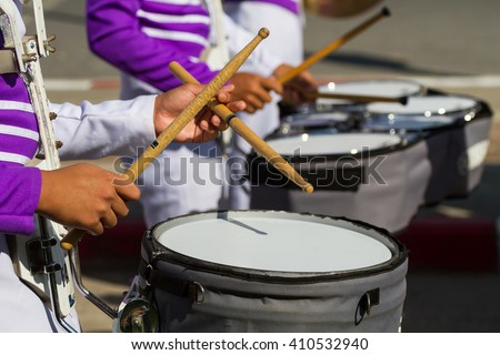 purple shirt musician in marching band playing drum with drumstick on band background - stock photo
