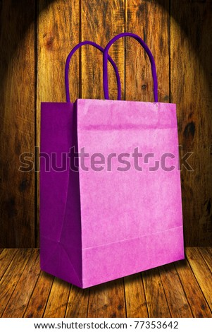 Purple shopping bag recycle paper on wood background - stock photo