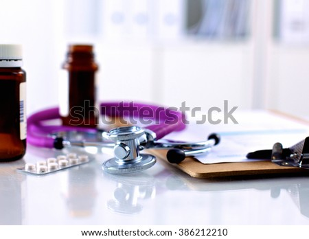 Purple stethoscope and pills on a laptop computer - stock photo