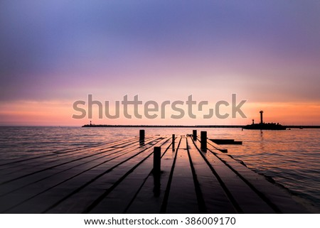 Purple sunset on sea with pier