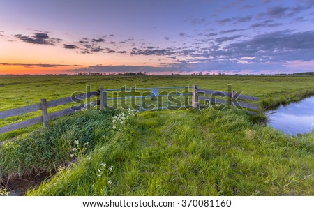 Purple sunset over fence in dutch polder landscape near Groningen