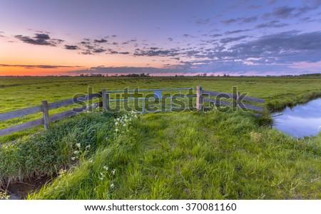 Purple sunset over fence in dutch polder landscape near Groningen - stock photo