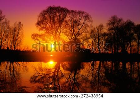 Purple sunset over lake - stock photo