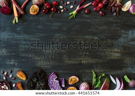 Purple toned fruit and vegetables fresh produce on dark distressed background, plenty of copy space design element for poster, book covers, recipes, website - stock photo