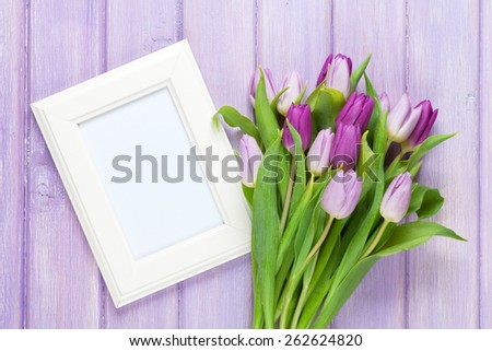 Purple tulip bouquet and blank photo frame. Top view over wooden table - stock photo