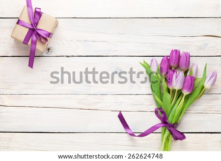 Purple tulips and gift box over wooden table. Top view with copy space - stock photo