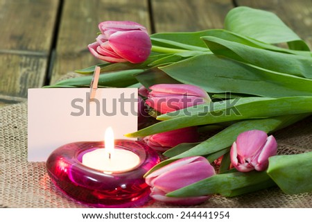 Purple tulips on an old wooden table