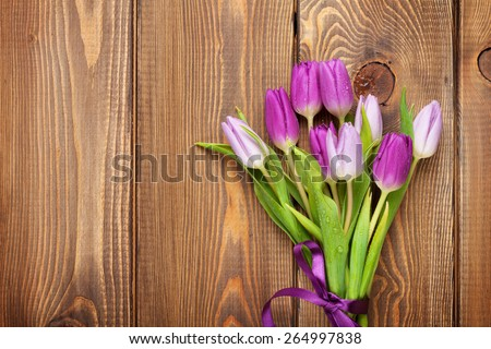 Purple tulips over wooden table. Top view with copy space - stock photo