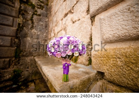 Purple wedding bouquet on the wall of an old building in Montenegro - stock photo