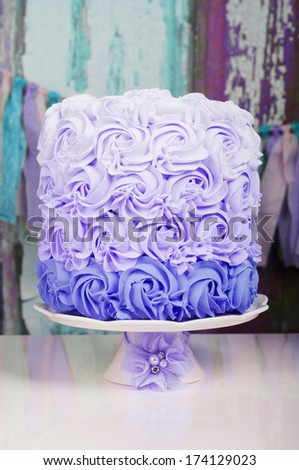 purple wedding cake on a cake stand with flower decoration