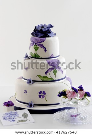 purple wedding cake with purple flower and invitation card - stock photo