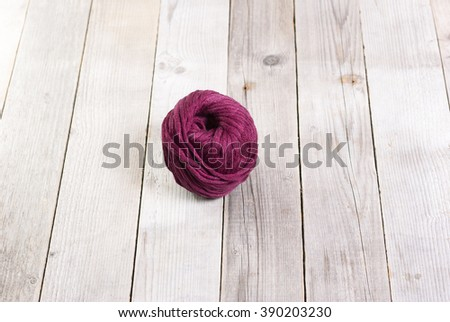 purple wool on weathered wood table background - stock photo