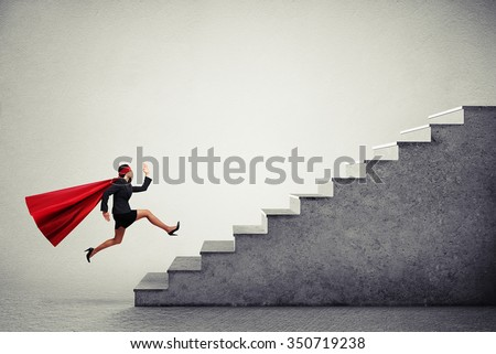 purposeful superwoman in red cloak running up stairs over light grey background - stock photo