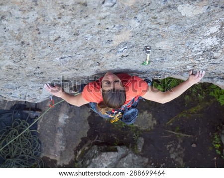 Purposeful young has been practicing climbing on the rocks. - stock photo