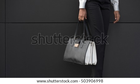 Purse close up hold by businesswoman against black wall as background.