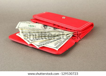 Purse with hundred dollar banknotes, on color background