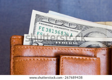 purse with hundred dollar banknotes on jeans background - stock photo