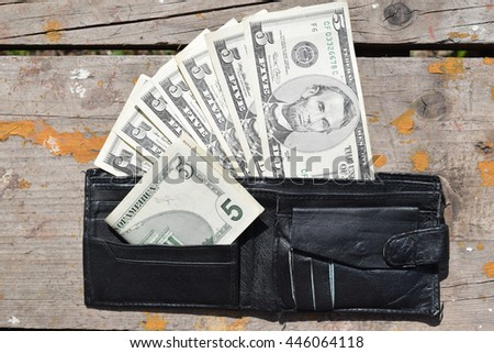 purse with money on a wooden table