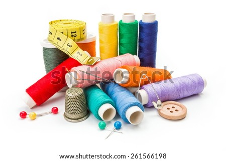 Push pins, safety pin, needles, thimble, measuring tape and colorful threads - stock photo