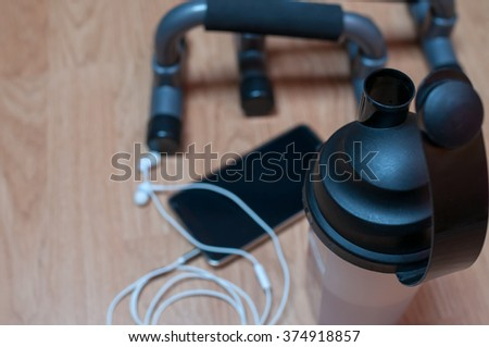 Push up bars, smart phone with earphones and water bottle on wooden background