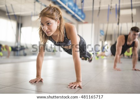 Push ups in gym with elastic rope