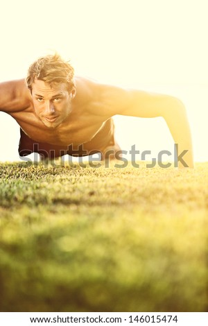 Push ups sport fitness man doing push-ups. Male athlete exercising push up outside in sunny sunshine. Fit shirtless male fitness model in crossfit exercise outdoors. Healthy lifestyle concept. - stock photo