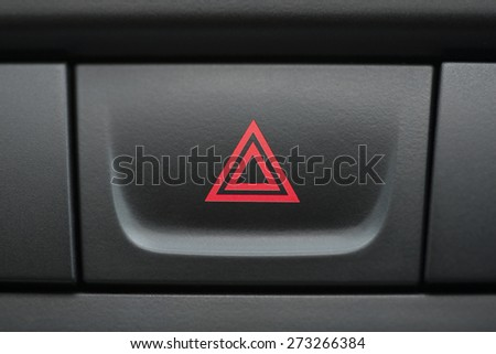 pushed red warning button with triangle pictogram, close up view and flasher light.  - stock photo