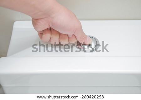 pushing a button to flush a closestool - stock photo