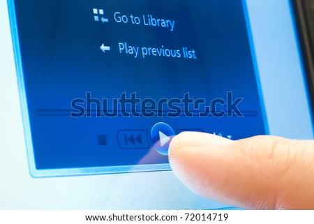 pushing play button on touch screen device - stock photo