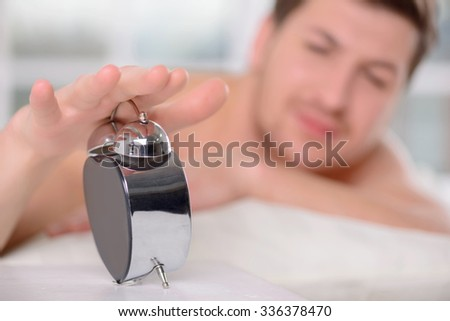 Pushing the off-button. Appealing young man sleepily turns off the alarm clock.  - stock photo