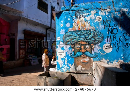 PUSHKAR, INDIA - FEB 12: Street graffiti with mustachioed man in turban on the blue wall of city on Fabruary 12, 2015. With population of 15,000, Pushkar is a popular touristic town in Ajmer district