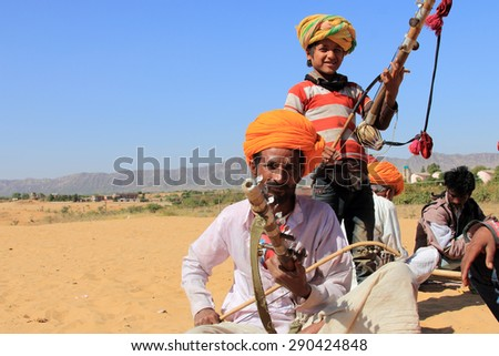 PUSHKAR, INDIA - FEB 5: Unidentified nomads plays ravanahatha in the deserts on February 05, 2015 in Pushkar, India. Ravanahatha is an ancient instrument used by traditional folk singers in India. - stock photo