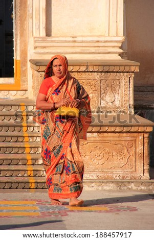PUSHKAR, INDIA - FEBRUARY 24: An unidentified woman walks out of the temple on February 24, 2011 in Pushkar, India. Pushkar is one of the five sacred pilgrimage sites for devout Hindus.