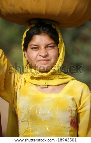 Pushkar, India - May 2008. Young Rajastani woman carrying container for flower farming and holy festivals. - stock photo