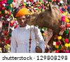 PUSHKAR, INDIA - NOVEMBER 22: Camel and his unidentified owner attends at traditional camel decoration competition at camel mela in Pushkar on November 22,2012 in Pushkar, Rajasthan, India - stock photo