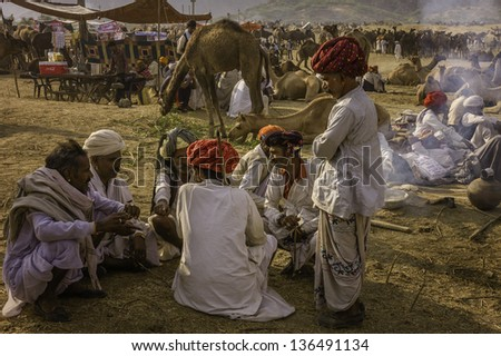 PUSHKAR, INDIA - NOVEMBER 04: Group of camel traders discus the sale and purchase of camels in the open desert at the annual camel fair on November 04, 2011 in Pushkar, Rajasthan, India.