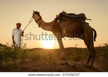 Pushkar, India - November 05, 2014 : Unidentified Camel Trader crossing the sand dune during sunset  at sunset point during Camel Fair in Pushkar, India.