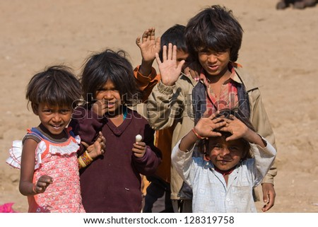 PUSHKAR, INDIA - NOVEMBER 18:  unidentified children at the Pushkar Camel Mela on November 18,2012 in Pushkar, Rajasthan, India. This fair is the largest camel trading fair in the world. - stock photo