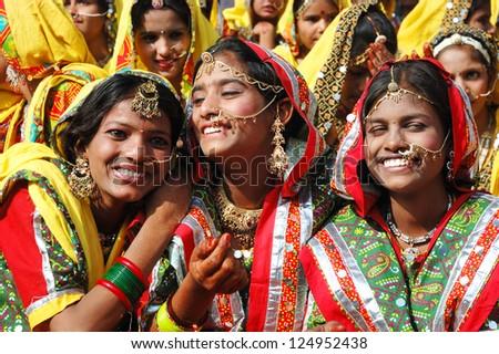 PUSHKAR, INDIA - NOVEMBER 21: Unidentified indian girls are preparing to dance  at annual Thar desert camel fair in Pushkar on November 21,2012 in Pushkar,Rajastan,India - stock photo
