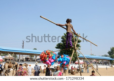 PUSHKAR, INDIA - NOVEMBER 12:Unidentified rope-walker are preparing to circus perfomance in nomadic camp during traditional camel fair holiday in Pushkar on November 12,2013 in Pushkar,Rajasthan,India
