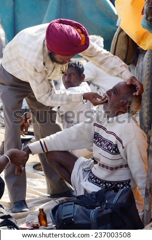 PUSHKAR, INDIA - NOVEMBER 13:Unidentified Sikh dentist treats old man teeth during traditional camel fair at Pushkar, on November 13,2013 in Pushkar, Rajasthan, India.It's largest camel fair in Asia - stock photo